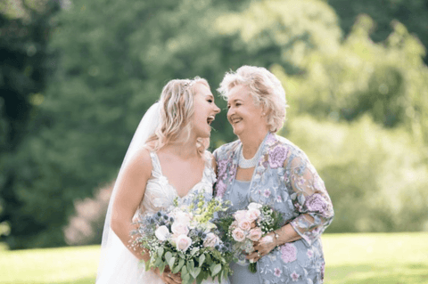 mother and bride smiling, wedding dress, blue dress