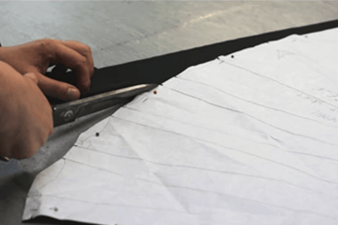 Picture of someone cutting out a fabric pattern with scissors on a cutting table.
