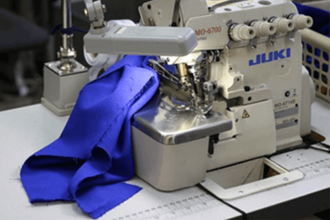 Picture of a Juki sewing machine with fabric being sewn into a dress.