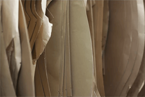 Close up picture of tailoring paper patterns hanging up in a row.