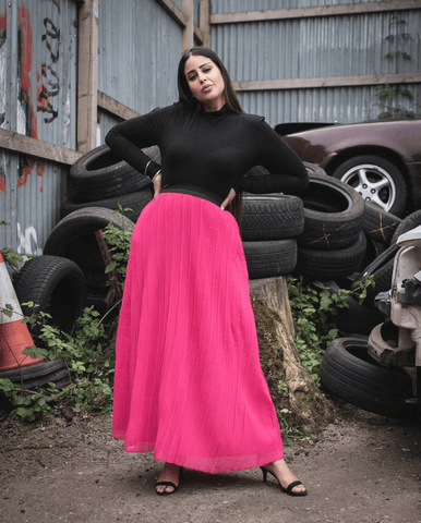 model in bright pink skirt and black high neck top
