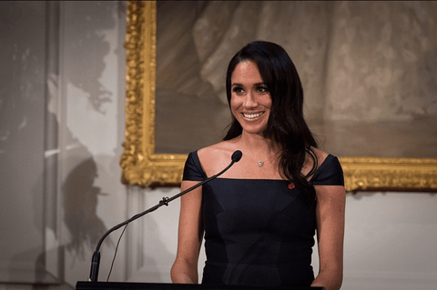 Meghan Markle giving a speech in a black boat neck dress