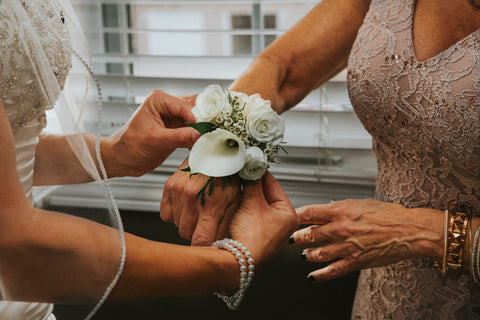 bride and her mother with a white corsage