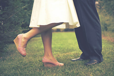 Couple standing in grass, wedges, white dress