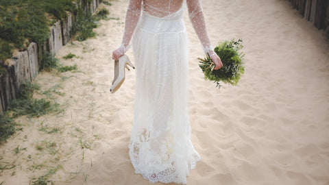bride walking along the beach carrying her shoes