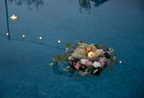 flowers and candle floating in water