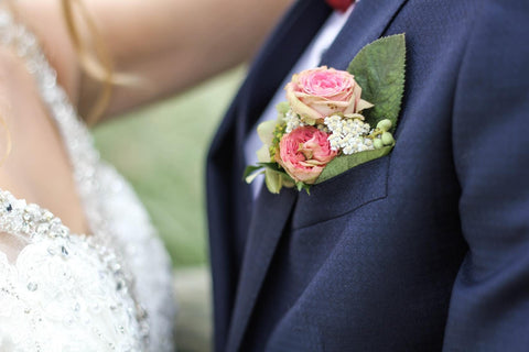bride and groom standing close together, groom with buttonhole flowers in jacket