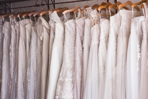 wedding dresses hanging up in a line