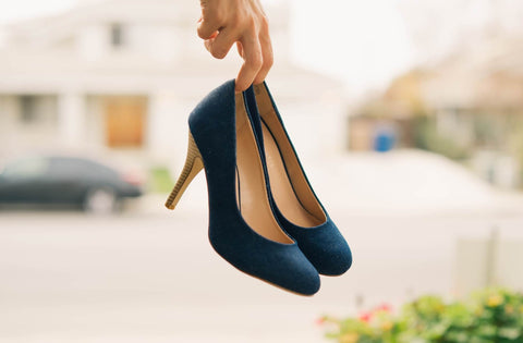 blue heels being carried in hand