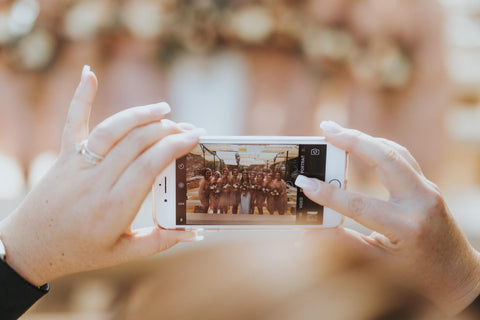 woman taking photo of wedding party