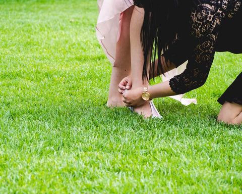 woman helping another women with her shoes on grass