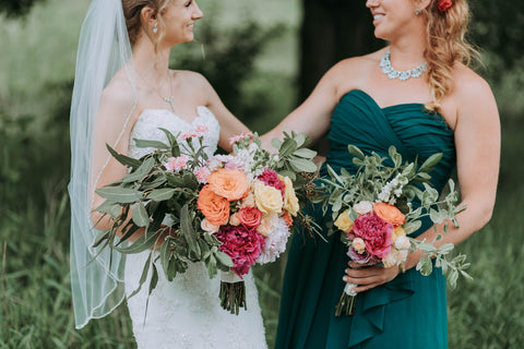 bride and bridesmaid in dresses with no sleeves