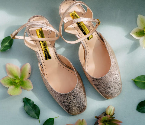 gold heeled shoes on blue background with flowers