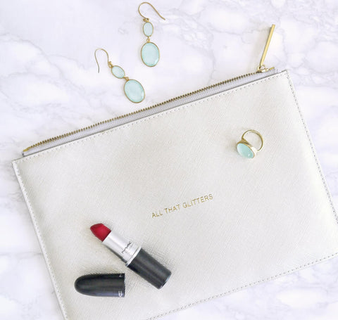 white bag on white background with red lipstick and blue earrings and bracelet on top