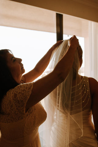 mother putting veil on brides head