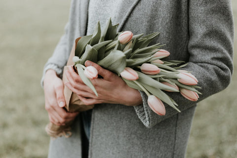 woman wearing grey jacket holding pink flowers