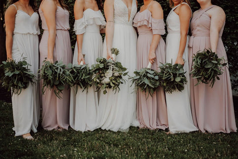 bridesmaids and brides in dresses with flowers