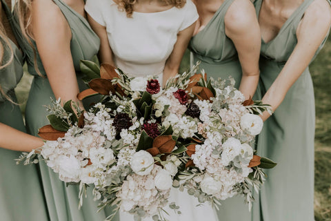 bride and bridesmaids in light green dresses holding flowers