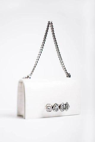 white handbag with silver chain and jewelled front