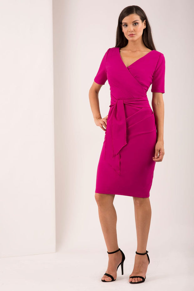 A brunette Model is wearing a wrap pencil dress by Diva Catwalk iin magenta