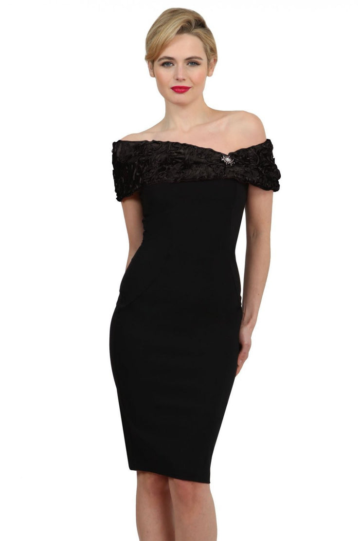 Model wearing the Diva Cornelli Perth dress with cornelli lace top, off shoulder design and diamanté brooch in black and black front image