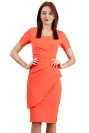 model wearing Diva Catwalk Katia short sleeve dress with an overlapped skirt and pleating across the tummy in hot coral front
