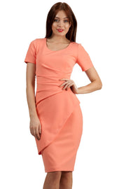 model wearing Diva Catwalk Katia short sleeve dress with an overlapped skirt and pleating across the tummy in tropical peach front