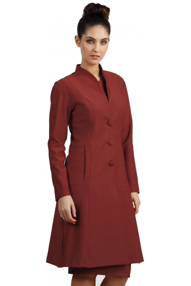 brunette model wearing diva catwalk couture fine raquella coat with buttons across the front and long sleeves with high neck and pockets in garnet red colour front