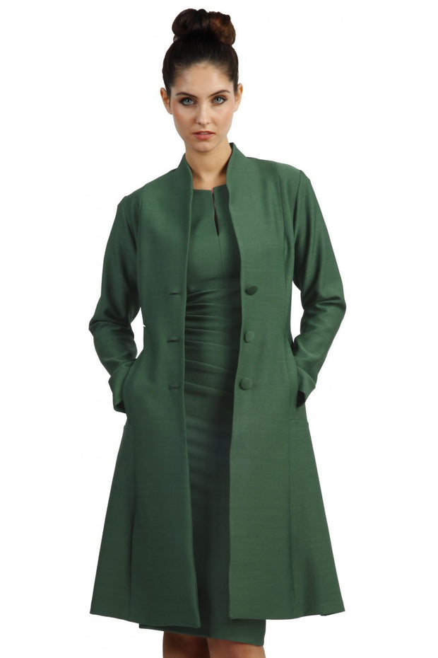 brunette model wearing diva catwalk couture fine raquella coat with buttons across the front and long sleeves with high neck and pockets in chrome green colour front