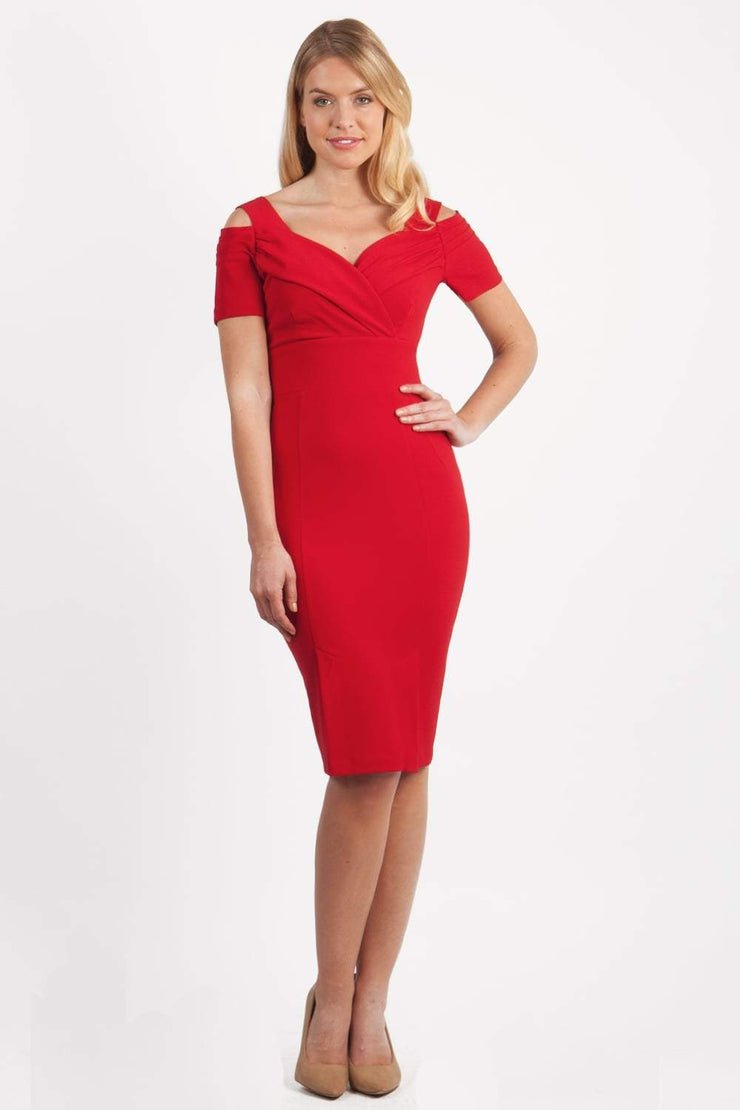 brunette model wearing diva catwalk amorette pencil skirt dress with a cold shoulder detaul and pleating across the bust and slit on a side of skirt in scarlet red front