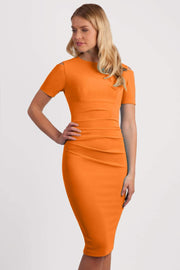Model wearing the Diva Atlas Pencil dress with round neckline short sleeved dress with small cutouts on the shoulders in sun orange front image