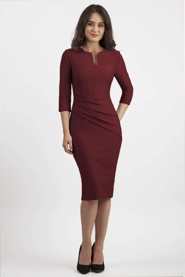 brunette model wearing seed diva catwalk milton sleeved pencil dress with a rounded neckline with a split in the middle in port royal front
