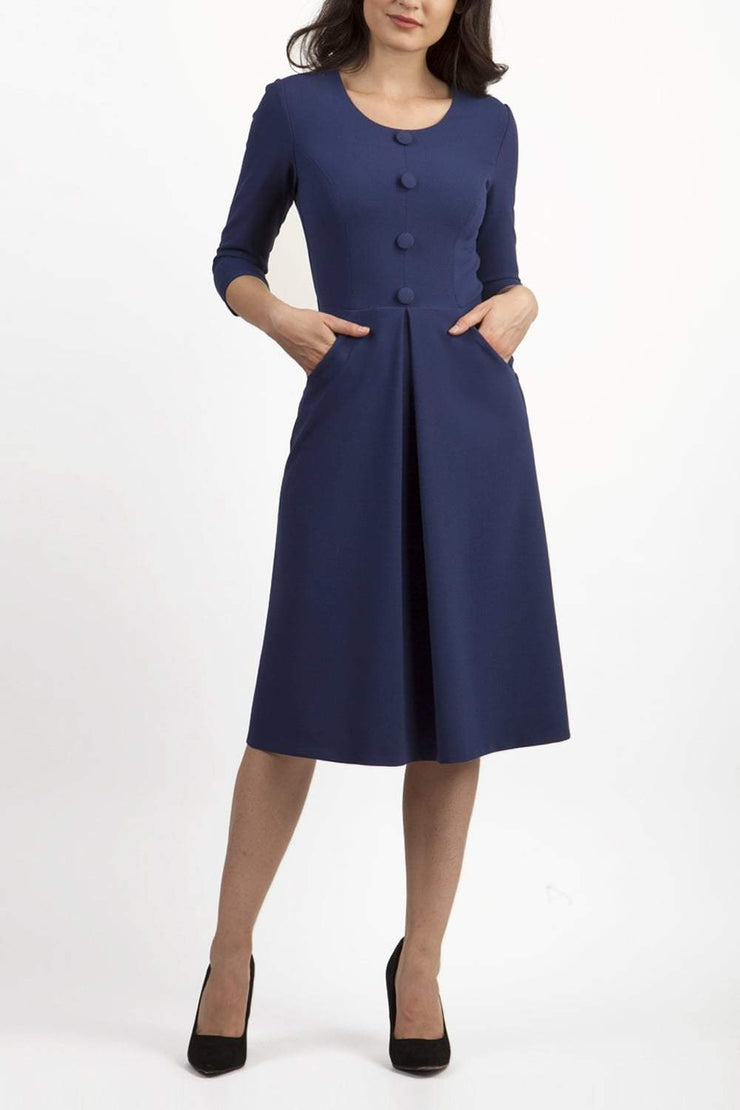 brunette model wearing diva catwalk waddeston swing a-line skirt dress with sleeves and pockets on side in colour navy blue front