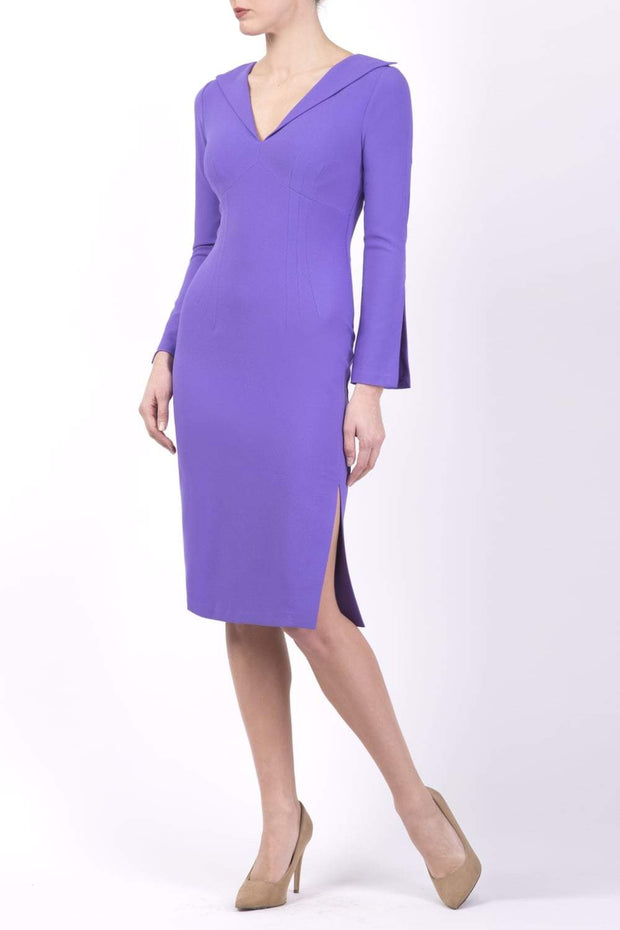 brunette model wearing diva catwalk chloe pencil skirt dress with long sleeves with deep slit and low v-neckline with tuxedo collar detailing in opulent violet colour front