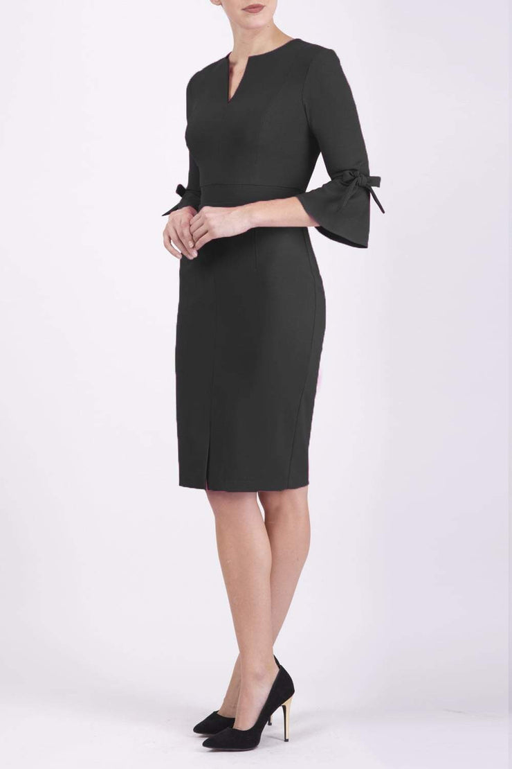 blonde model wearing diva catwalk zoe 3 4 sleeve formal dress with a split rounded neckline and split on skirt in black colour front