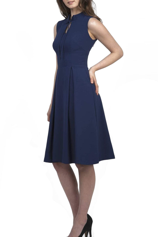 brunette model wearing diva catwalk oceana a-line swing skirt sleeveless dress with funnel neckline and tie detail in navy blue front