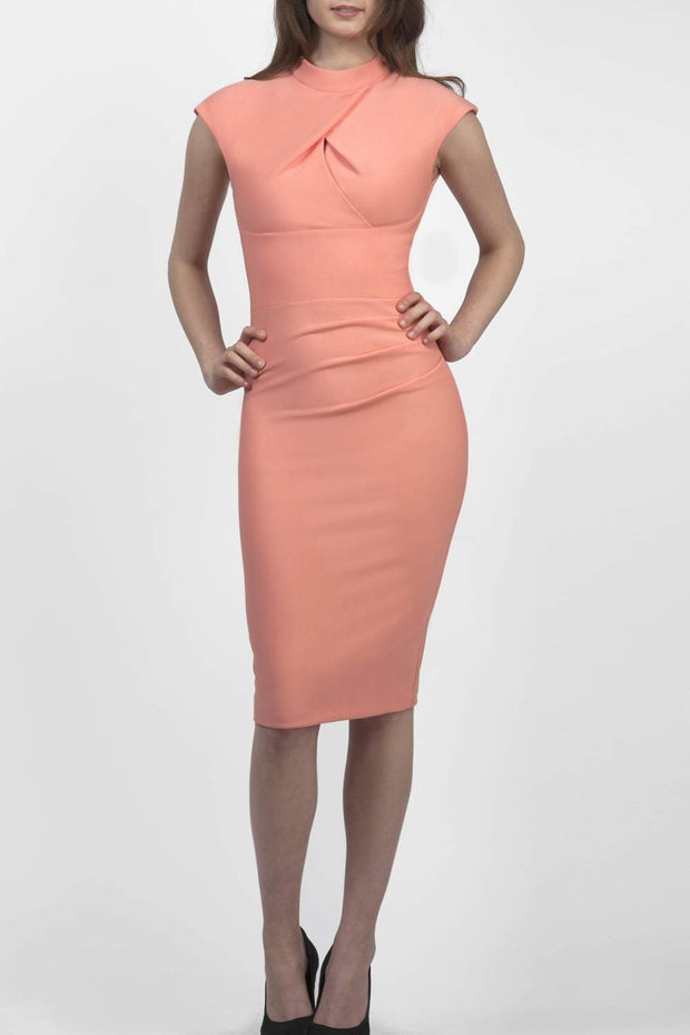 brunette model wearing diva catwalk beyonce pencil fitted dress with high neckline without sleeves with a wide band and pleating across the tummy area with a crossed detail neckline in colour peach front
