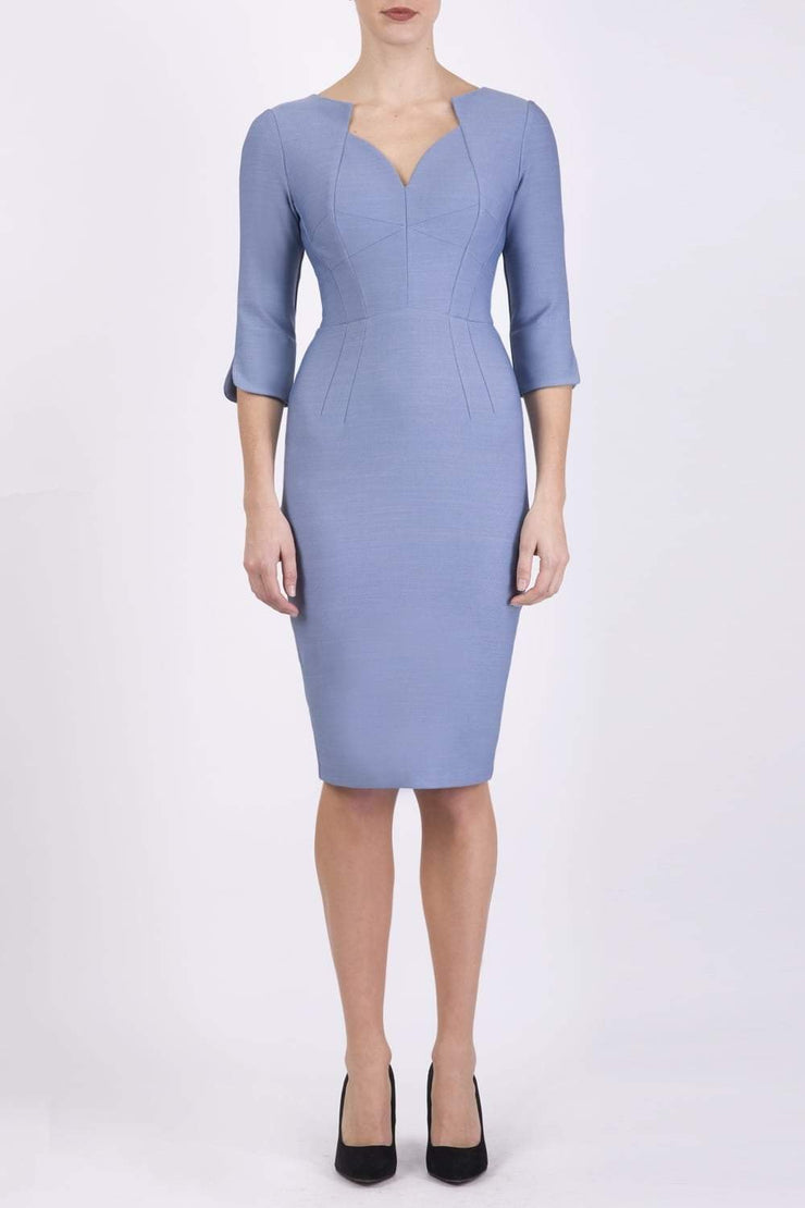 model wearing seed couture zara pencil skirt dress in pale blue with asymmetric neckline with sleeves front