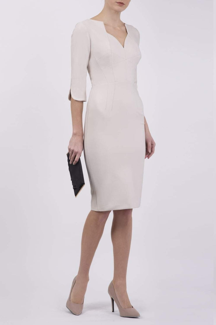 model wearing seed couture zara pencil skirt dress in sandy cream white with asymmetric neckline with sleeves front