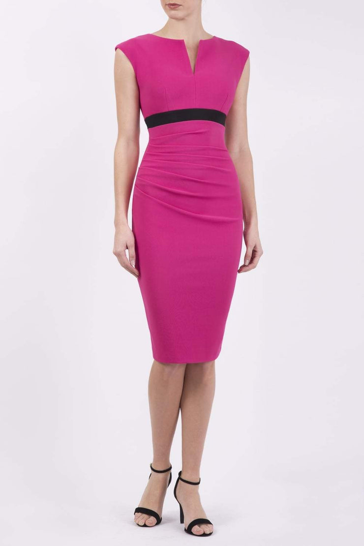 brunette model wearing diva catwalk nadia sleeveless pencil dress in pink colour with a contrasting black band and exposed zip at the back with a rounded neckline with a slit  in the middle front