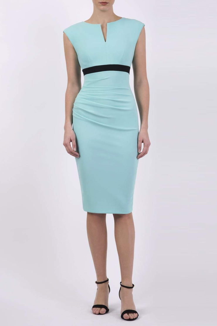 brunette model wearing diva catwalk nadia sleeveless pencil dress in mint green colour with a contrasting black band and exposed zip at the back with a rounded neckline with a slit  in the middle front