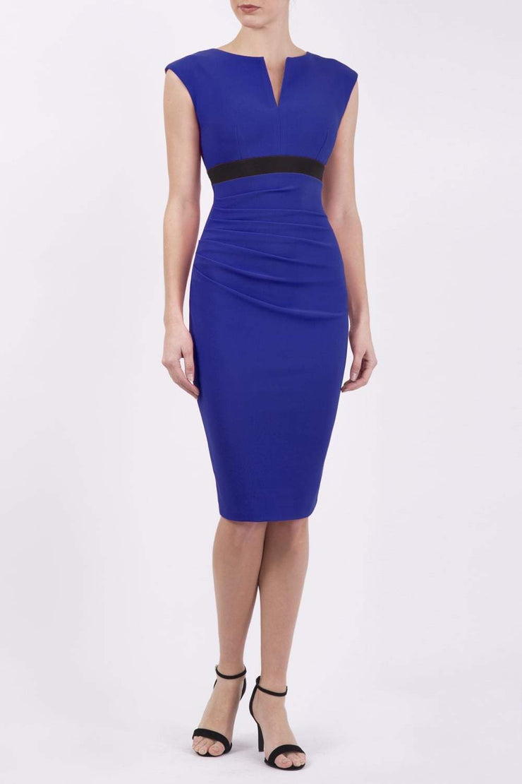 brunette model wearing diva catwalk nadia sleeveless pencil dress in cobalt blue colour with a contrasting black band and exposed zip at the back with a rounded neckline with a slit  in the middle front