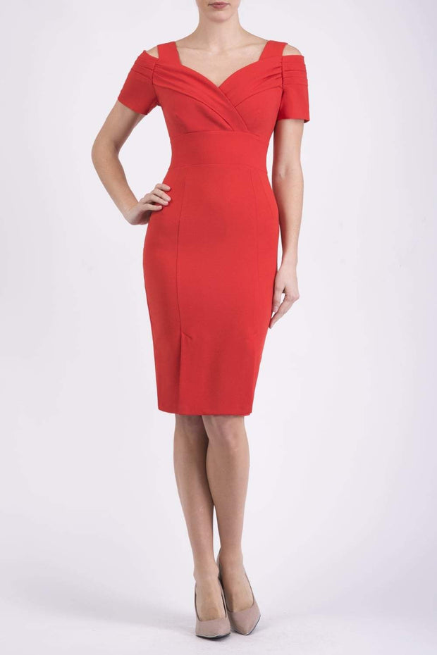 Model wearing the Diva Amorette dress with cold shoulder and pleated detailing on the arms in fiesta orange front image