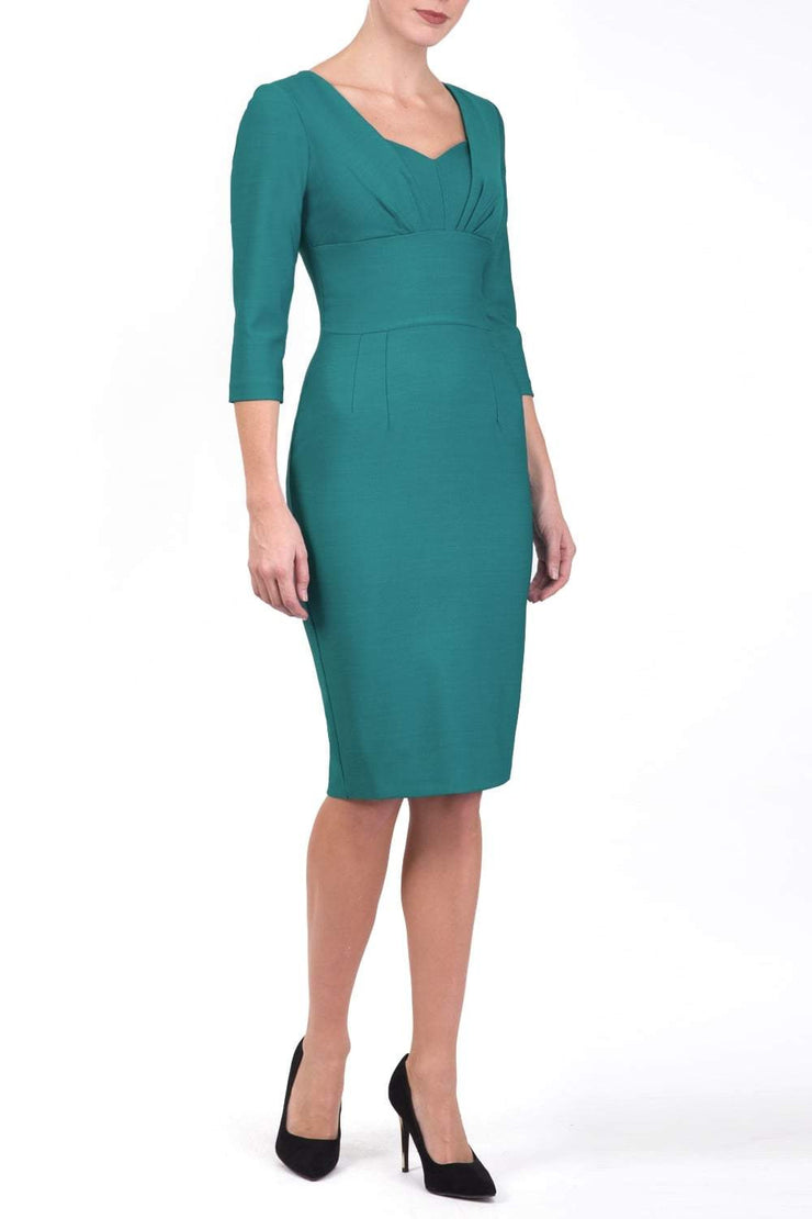 Model wearing Diva Catwalk Seed Greenwich tree quarter sleeve knee length v-neckline dress with pleating detail across the bust and broad waistband in Harbour Green front