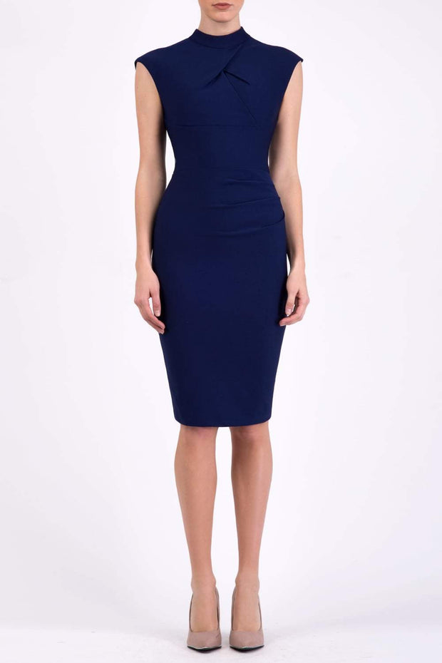brunette model wearing diva catwalk beyonce pencil fitted dress with high neckline without sleeves with a wide band and pleating across the tummy area with a crossed detail neckline in navy blue  front