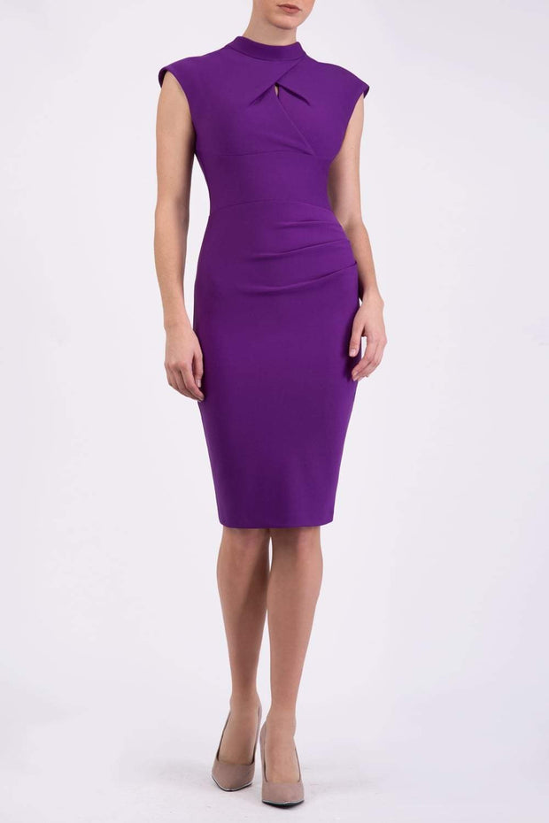 brunette model wearing diva catwalk beyonce pencil fitted dress with high neckline without sleeves with a wide band and pleating across the tummy area with a crossed detail neckline in royal purple front