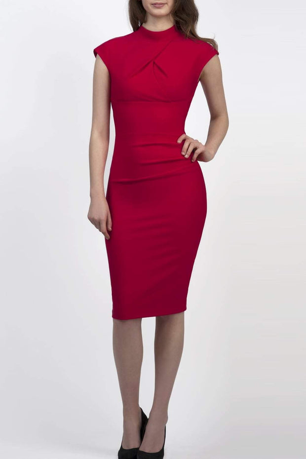 brunette model wearing diva catwalk beyonce pencil fitted dress with high neckline without sleeves with a wide band and pleating across the tummy area with a crossed detail neckline in rose red front