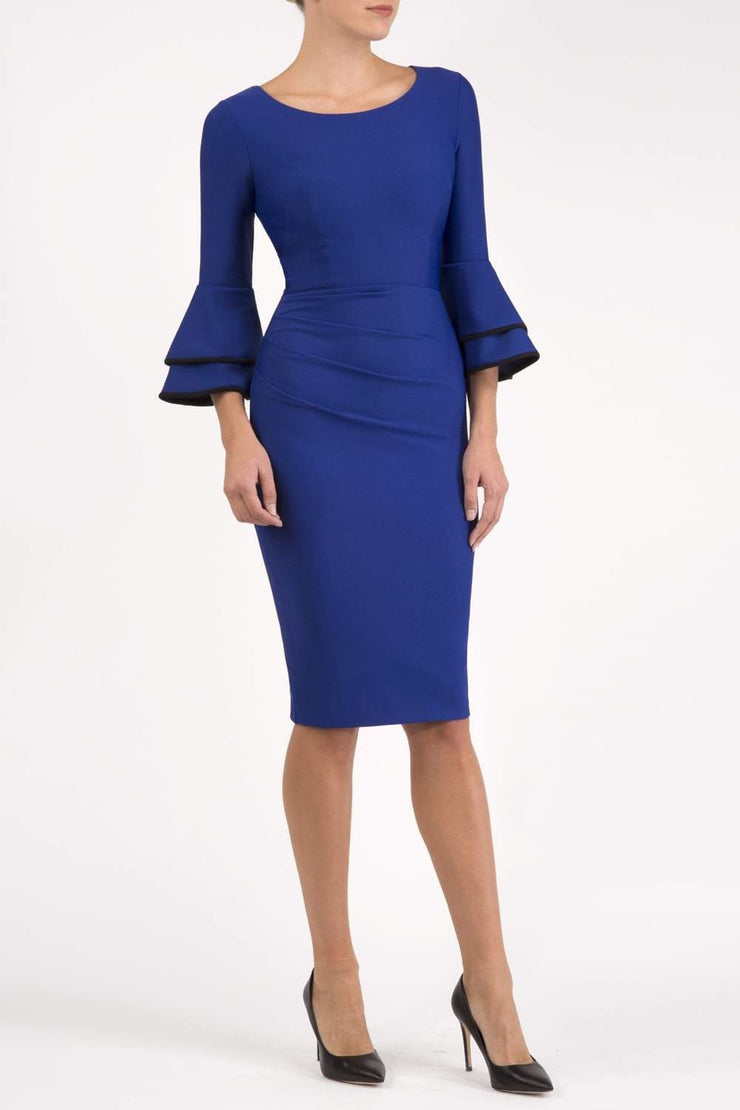 blonde model wearing diva catwalk tina pencil skirt dress with rounded neckline and flute sleeve in cobalt blue front