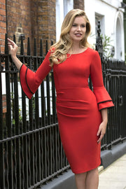 blonde model wearing diva catwalk tina pencil skirt dress with rounded neckline and flute sleeve in burnt orange front
