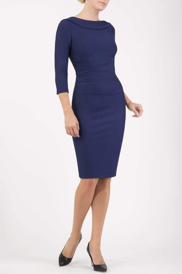 model wearing diva catwalk york pencil-skirt dress with sleeves and rounded folded collar and plearing across the tummy area in navy blue colour front